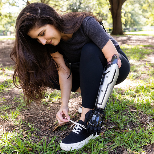 The image shows a woman tying her shoelace wearing the Nexus hand